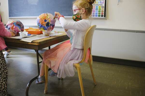 "Castle Island Bilingual Montessori school student Mia Finlan, 5, glues tissue paper to her lantern in the art studio on Thursday, Sept. 17, 2020, in Albany, N.Y. The students were creating lanterns for Friday's Desfile de Faroles, a lantern parade in the school's garden courtyard to celebrate the independence day's of five Central American countries. The dual language immersion school has lost almost half of their enrollment due to financial hardships of parents during the pandemic. ""We went from 40 children last school year to just 21 this year, we have the space to safely teach up to 50 students"", Diane Nickerson, founder and school director said. The school has had to furlough two teachers. (Paul Buckowski/Times Union)"
