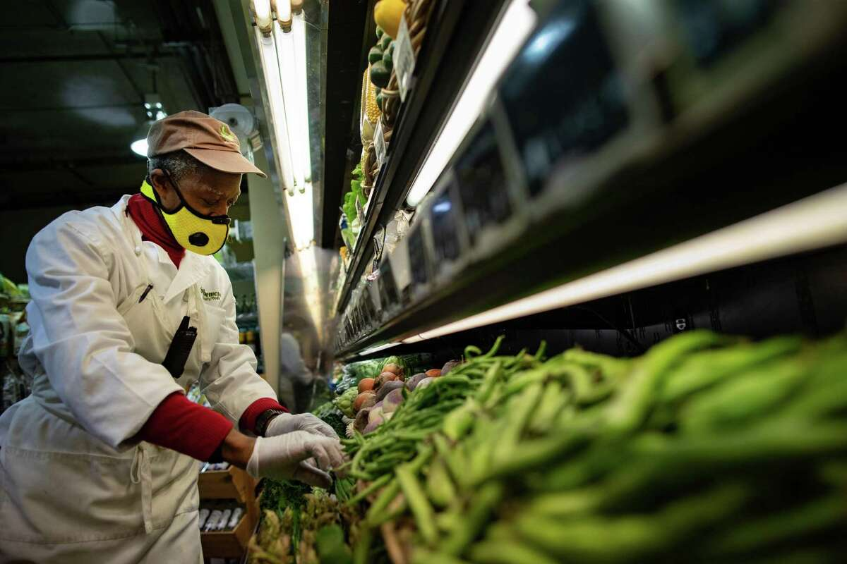 Phoenicia Specialty Food's employee Melvin Johnson, 61, wears a protective mask while working on the produce department, Wednesday, March 3, 2021, in Houston.