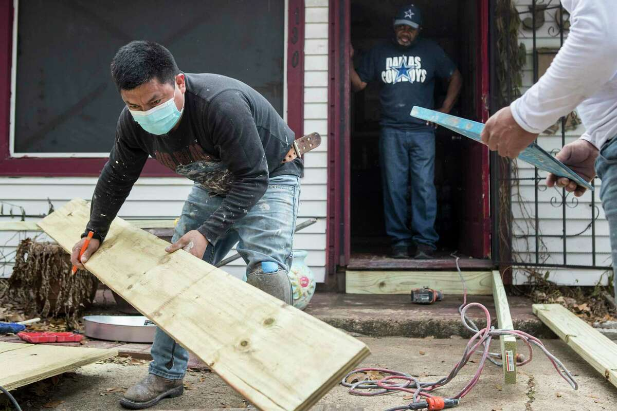 Marvin Mariquin, left, works to make repairs to Kenneth Castilow's home as part of a Houston Health Foundation, Houston Harris County Winter Storm Relief Fund and United Way of Greater Houston project.