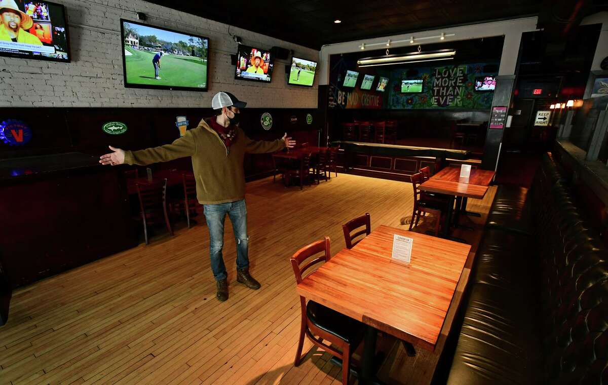 Blind Rhino owner Matt Bacco prepares his restaurant with socially distanced seating Friday, March 4, 2021, in Norwalk, Conn. The state issued a COVID restriction easement for restaurants allowing for more dining with specified distance between tables.