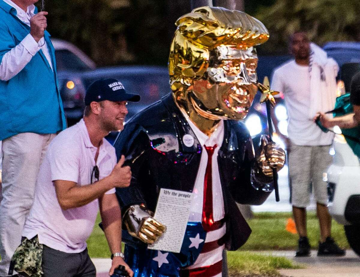 Supporters of former US President Donald Trump take pictures with a gold statue of him outside the hotel where the Conservative Political Action Conference 2021 (CPAC) was held in Orlando, Florida on February 28, 2021.