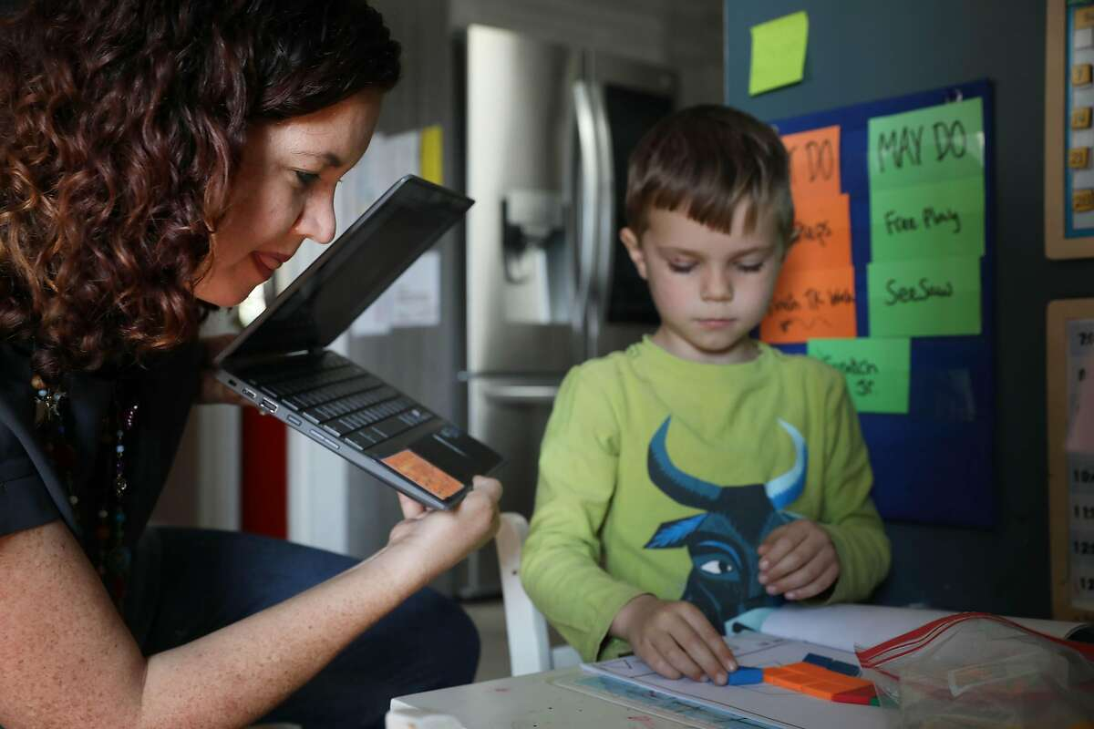 Jennifer Butterfoss, officer Campaign for Better San Francisco Public Schools, holds the camera on a laptop over the work of her son, James, 5, as he attends distance learning at Alvarado Elementary School.