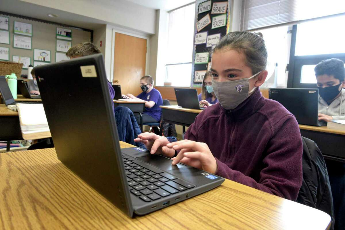 Eva Bauco, age 11, of Danbury, works during her sixth grade science class at St Joseph School.