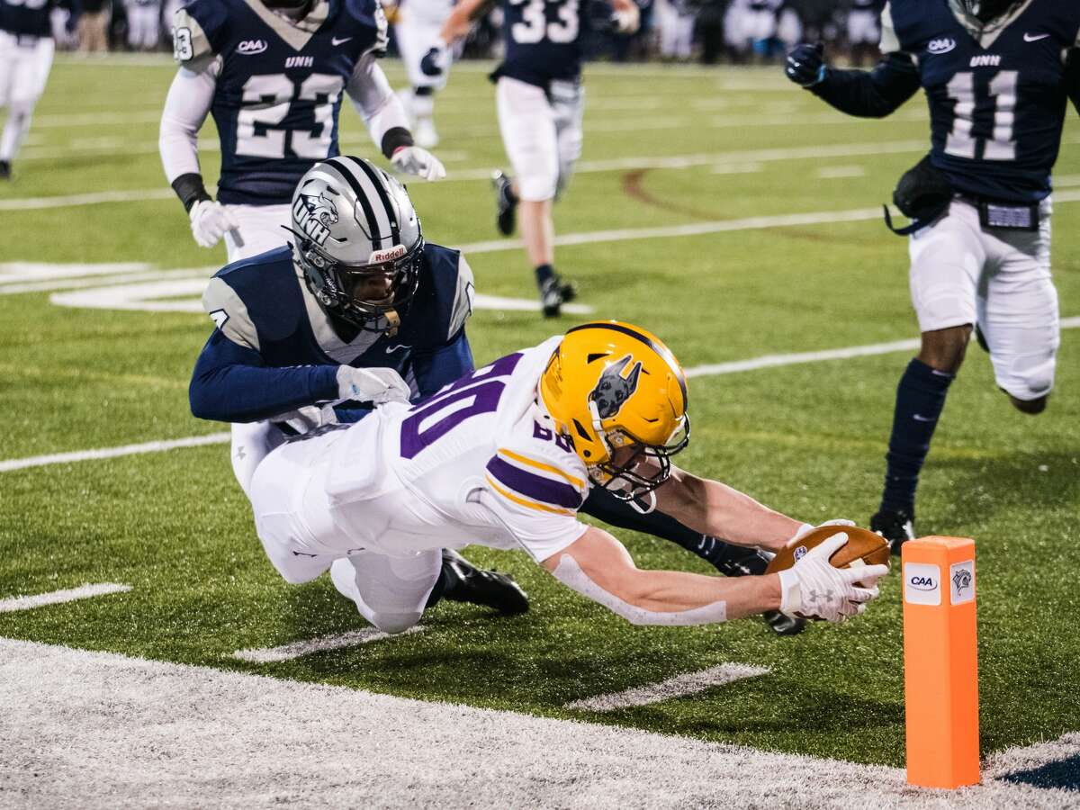 UAlbany redshirt freshman tight end Mike Gray dives for the pylon to score the Great Danes' first touchdown on a 23-yard reception from Jeff Undercuffler against New Hampshire in a Colonial Athletic Association football game Friday, March 6, 2021,in Durham, N.H. The UNH defender is sophomore cornerback Randall Harris. Gray caught four passes for 43 yards on the drive. (China Wong/UNH athletics)