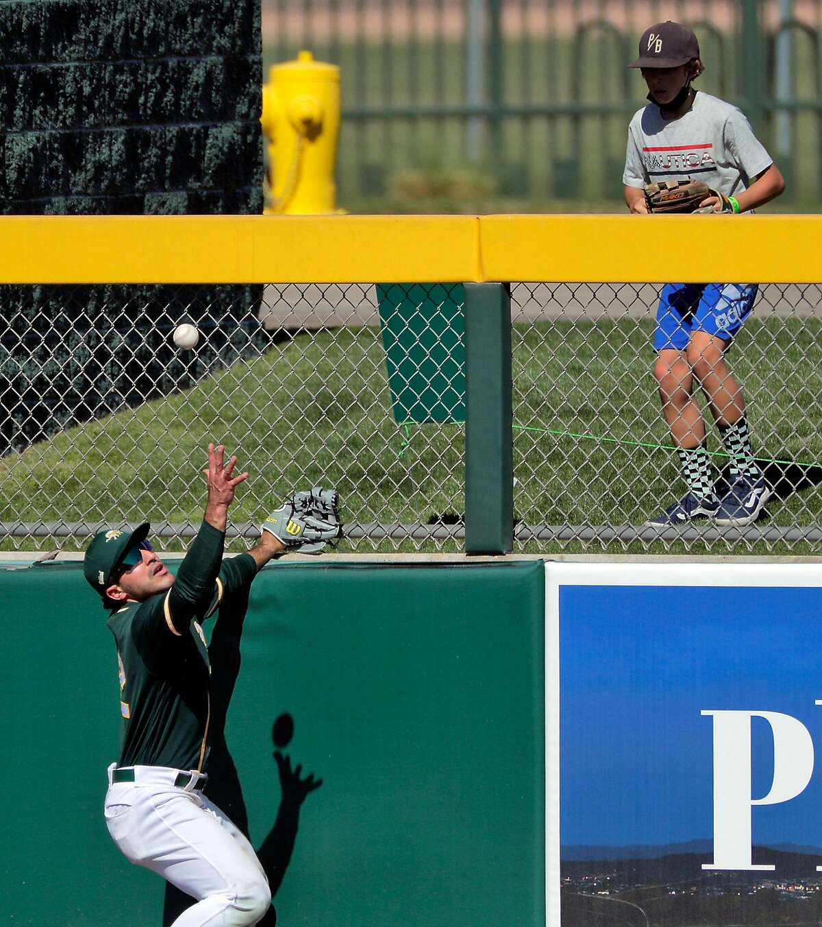 Ramon Laureano (22) grabs for a ball hit against the fence by Jose Iglesias (4) in the fourth inning as the Oakland Athletics played the Los Angeles Angels at Hohokam Stadium in Mesa, Ariz., on Friday, March 5, 2021.