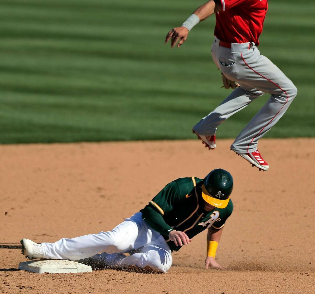 Greg Deichmann (31) ducks under shortstop Jeremiah Jackson (97) as Elvis Andrus (17) hit into a double play in the fourth inning as the Oakland Athletics played the Los Angeles Angels at Hohokam Stadium in Mesa, Ariz., on Friday, March 5, 2021.