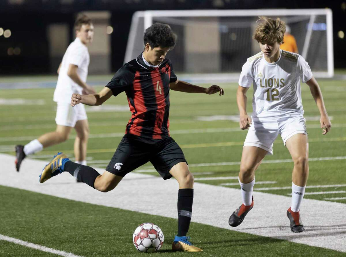 Porter Alexsander Hernandez (4) kicks the ball while under pressure from Lake Creek Jaye Morris (12) during the first half of a District 20-5A boys soccer at Randall Reed Stadium, Friday, March 5, 2021, in New Caney.