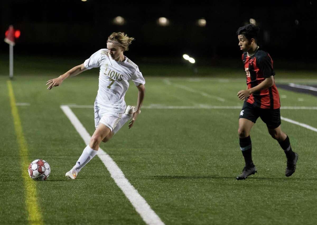 Lake Creek Tristen Schaefer (7) kicks the ball out of bounds due to pressure from Porter Jovany Garcia (10) during the first half of a District 20-5A boys soccer at Randall Reed Stadium, Friday, March 5, 2021, in New Caney.