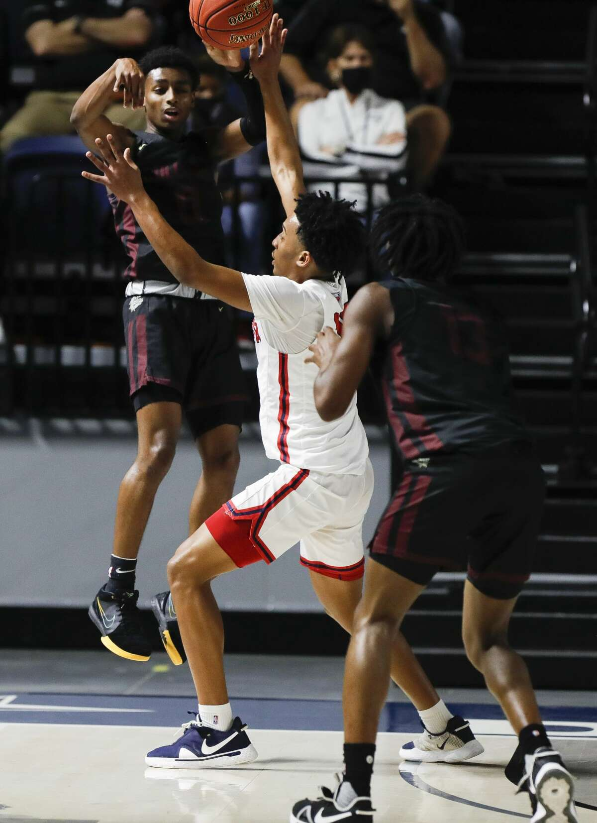 Summer Creek shooting guard Jaylon Johnson (0) makes a pass under pressure from Atascocita shooting guard Christian Asahby (11) to point guard Steven Sawyer (13) at Delmar Fieldhouse, Friday, March 5, 2021, in Houston.