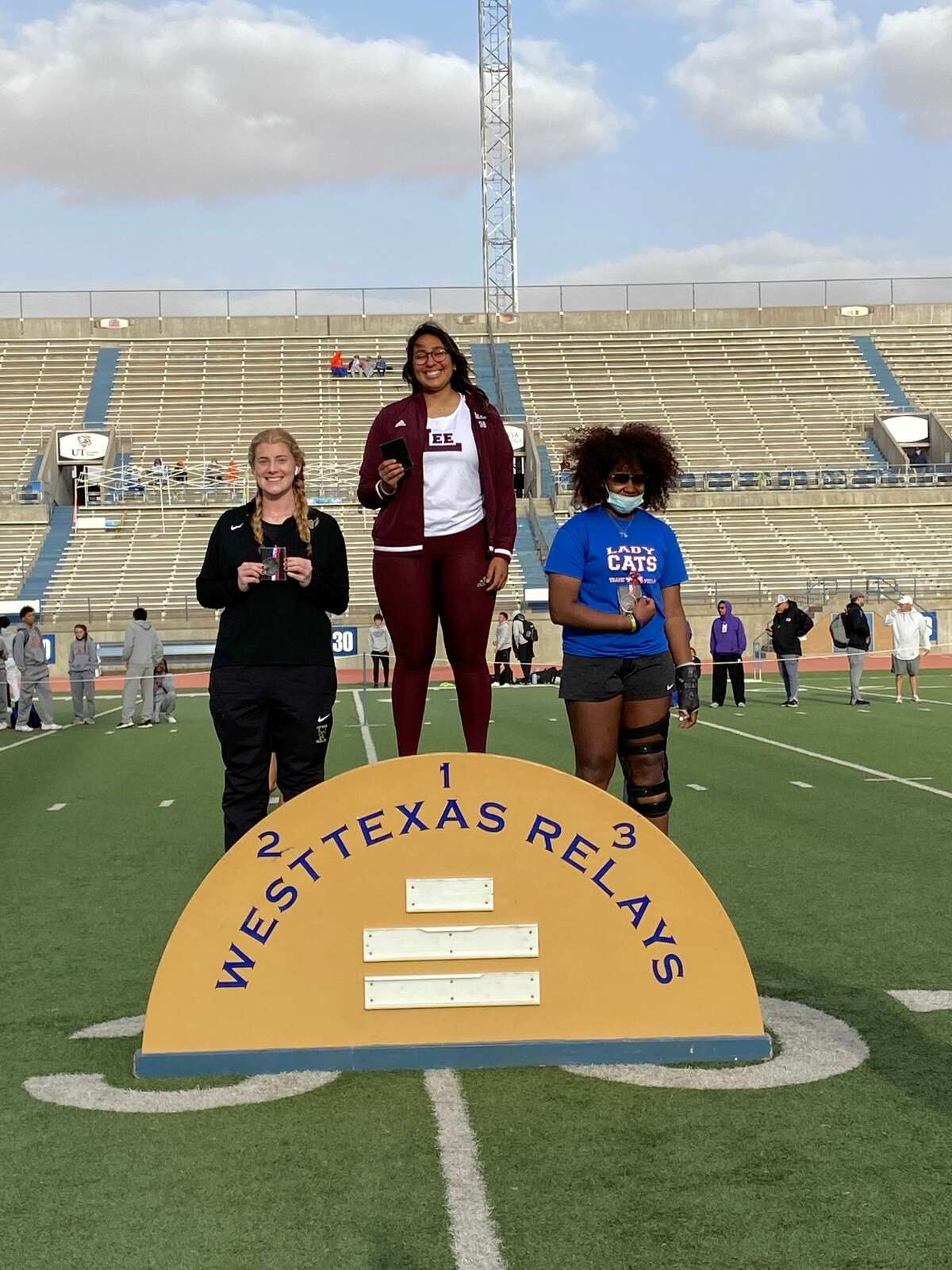 Lee thrower Leah Acosta stands atop the podium after winning gold in the shot put at the West Texas Relays on March 5 in Odessa. Andrews' Emily Burgen placed second.