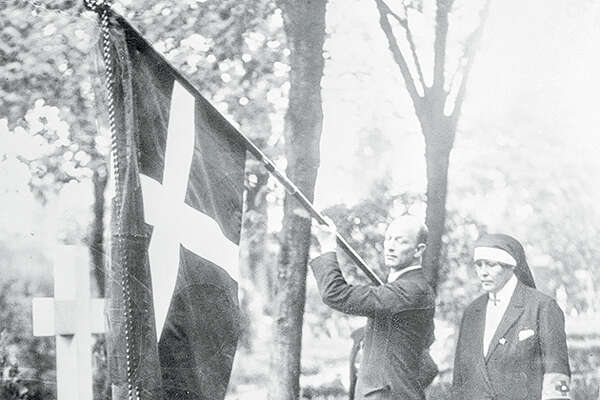 Kneeling before the tomb of a Danish war hero of 1895, Ruth Bryan Owen, first diplomatic minister of the United States, places a wreath and an American flag before the headstone of the patriotic shrine. The flag of Denmark flies overhead as a Danish Red Cross nurse (right) watches the ceremony.