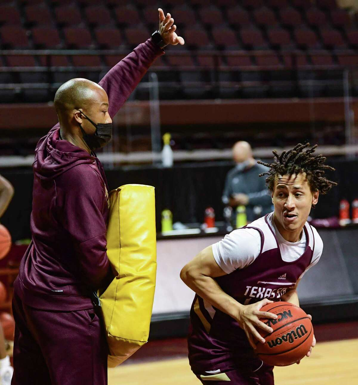 Texas State coach Terrence Johnson plays defense for guard Mason Harrell during the team's practice at Strahan Arena on Wednesday, March 3, 2021.