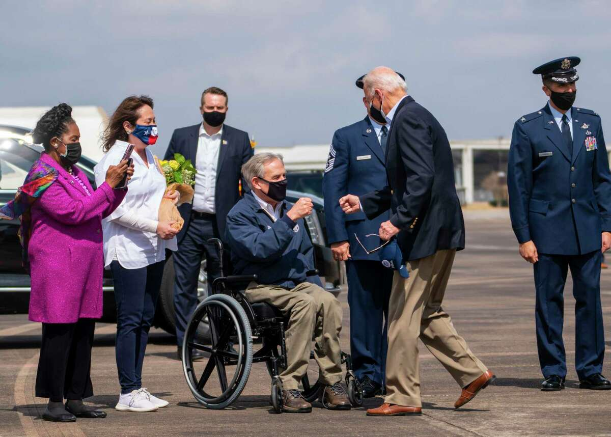 FILE -- President Joe Biden greets Texas Gov. Greg Abbott upon his arrival to assess damage from the winter storm in Houston, Feb. 26, 2021. Biden has since sharply criticized Texas for abruptly removing its mask mandate. (Doug Mills/The New York Times)