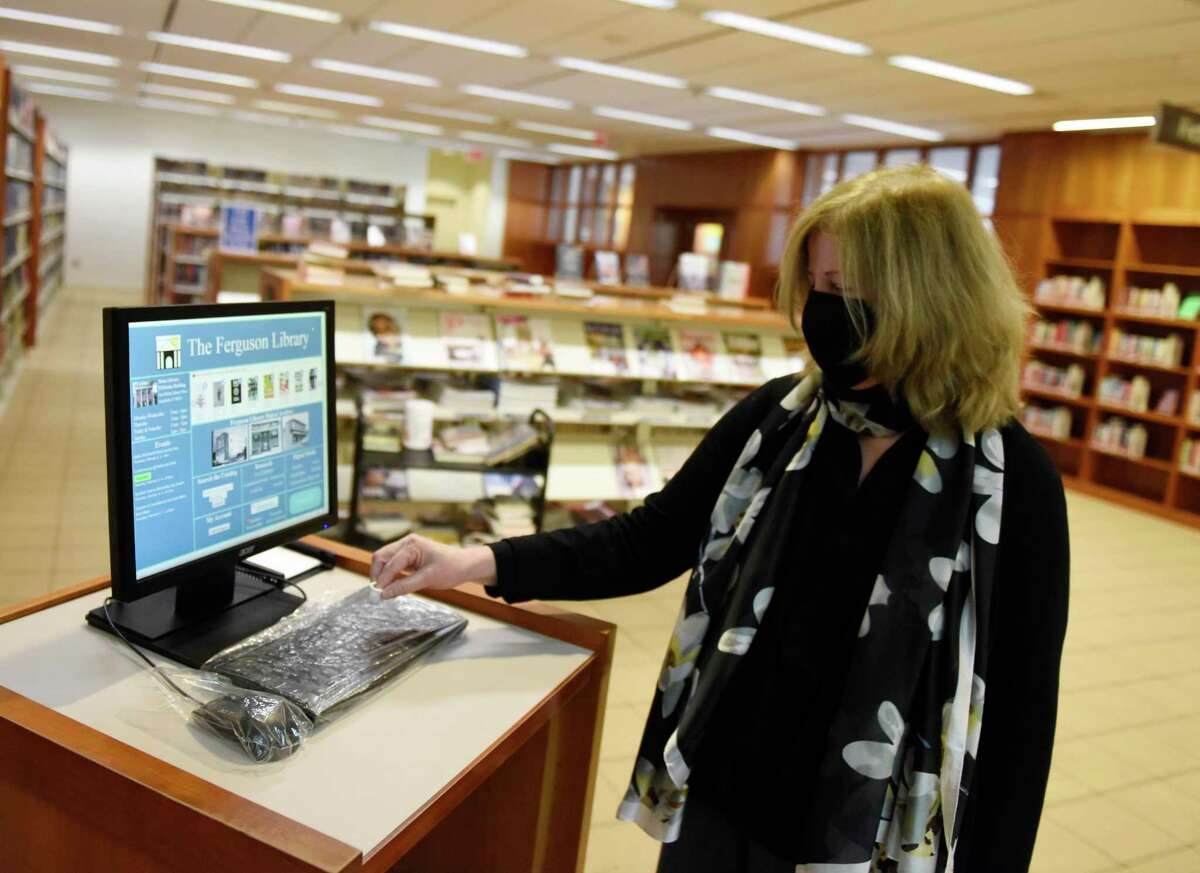 Library President Alice Knapp shows the plastic protected keyboard and mouse at the computer kiosks at Fergsuon Library in Stamford, Conn. Thursday, Feb. 4, 2021. Outside agencies got a cash infusion from the city's planning board in this year's budget recommendation, and the Ferguson Library was one of the organizations to reap the benefit.