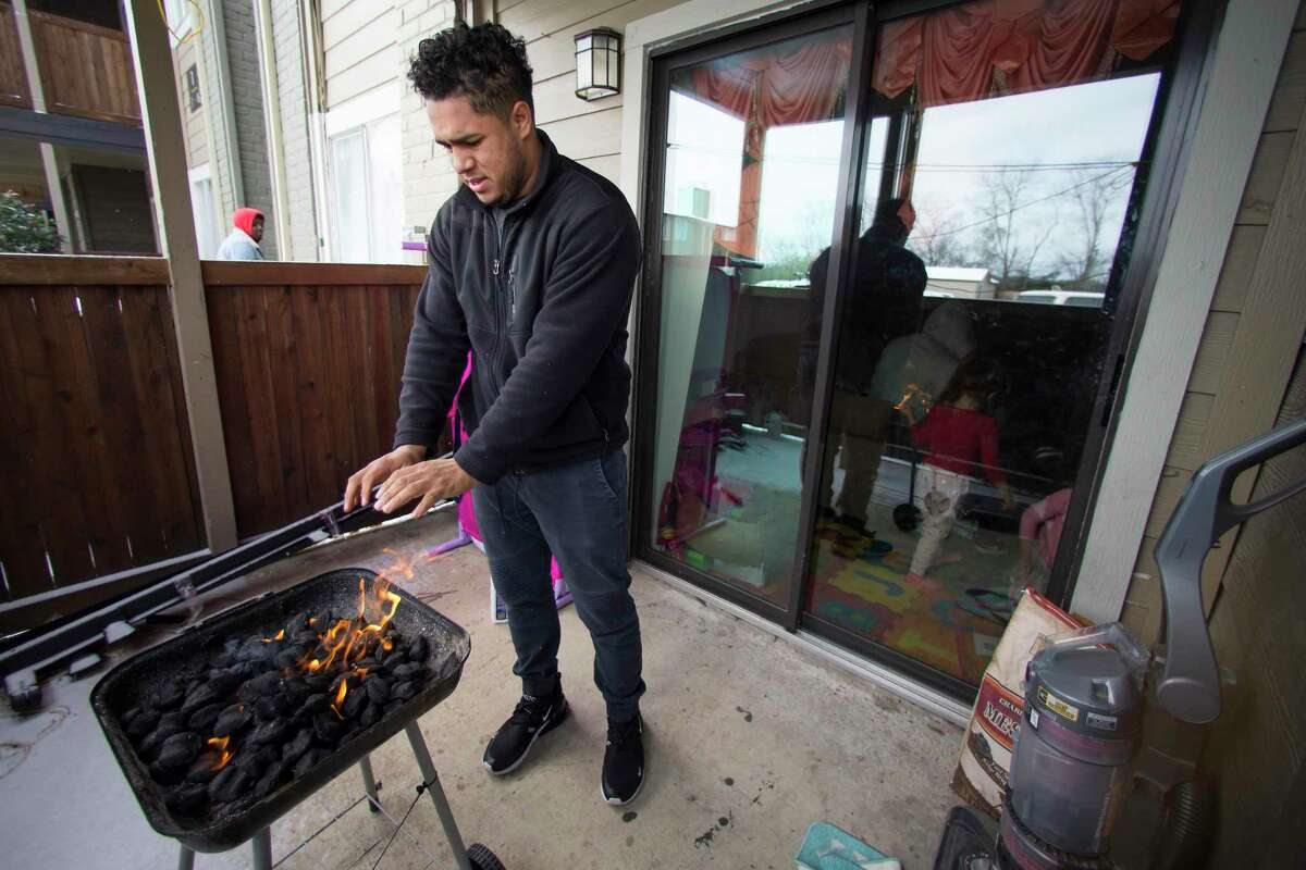 Kevin Morazan warms his hands after lightning his charcoal grill to cook after losing power in the Greenspoint area due to rolling blackouts during the recent winter storm. A deep freeze in 1989 brought even colder temperatures to Texas than the recent winter storm, but lights stayed. What happened to make the power grid less reliable in the intervening 30 years?