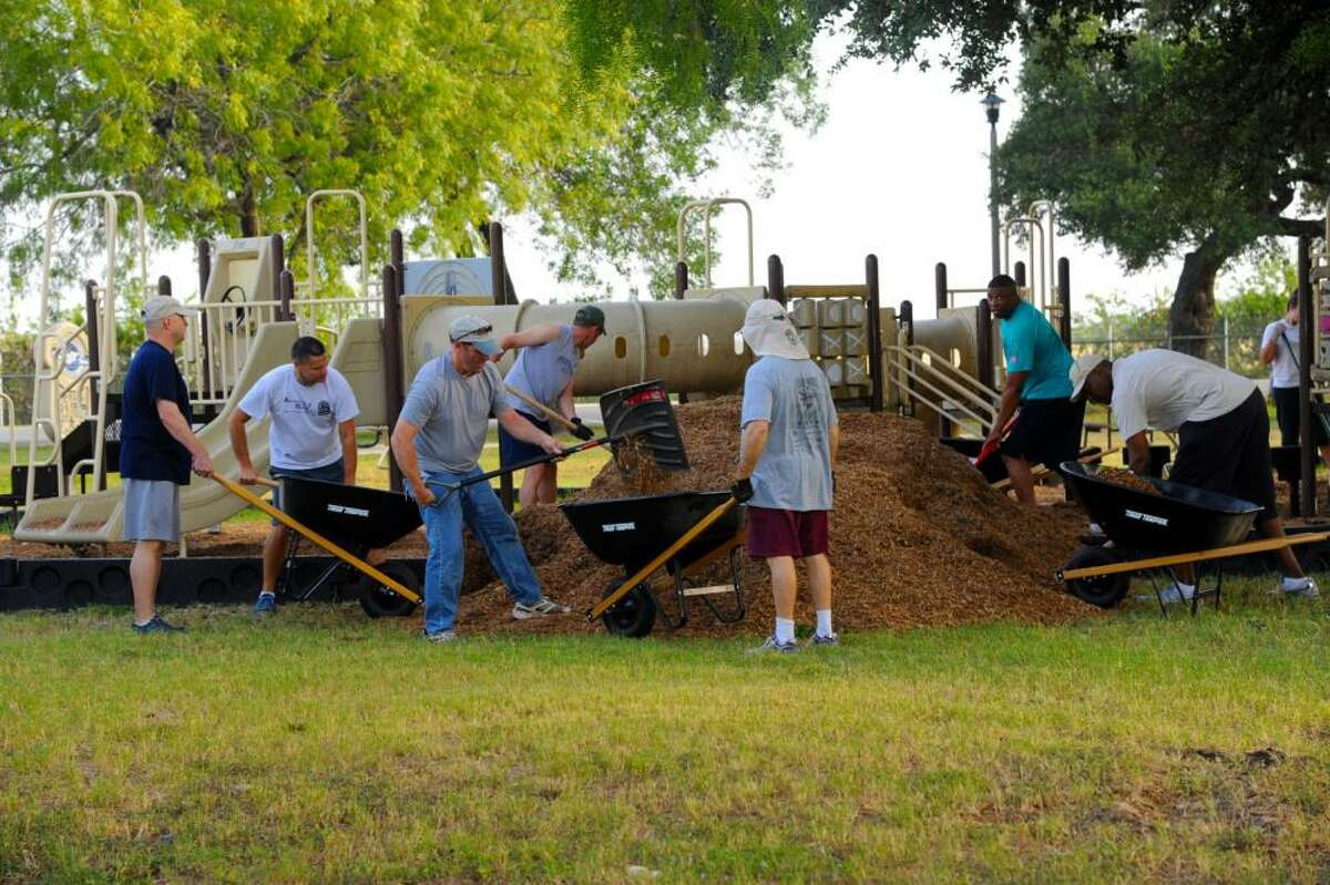 Volunteers spruce up a playground at Eberle Park, the family outdoor recreation center at JBSA-Randolph that was named in honor of Capt. Joseph N. Eberle, a pilot who died in 1953 in an air crash on base.