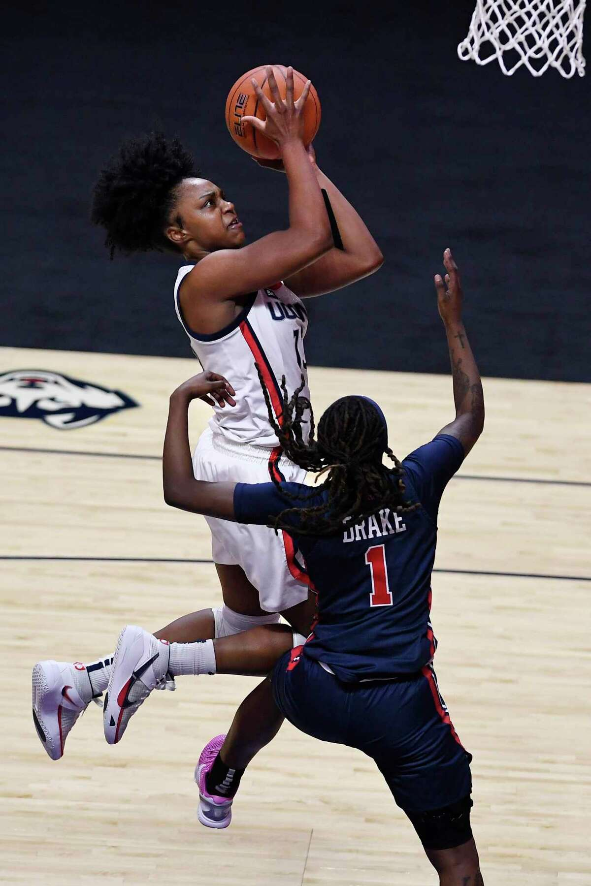 UConn's Christyn Williams, top, makes a basket while fouled by St. John's Unique Drake during the first half of the quarterfinals of the Big East Conference tournament at Mohegan Sun Arena on Saturday in Uncasville.