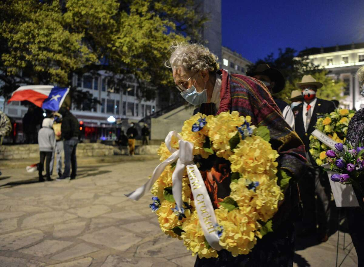 """Direct descendant Carolyn Cotton carries the wreath honoring David Crockett during the """"Dawn at the Alamo"""" ceremony Saturday morning commemorating the beginning of the siege of the Alamo in 1836."""
