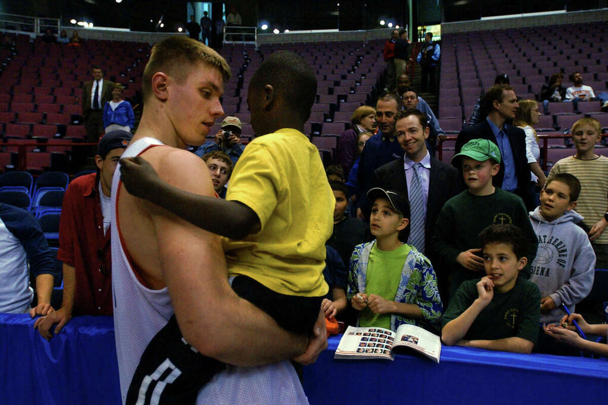 Syracuse University center Craig Forth picks 6-year-old Ethan Trudeau from a crowd of well-wishers at the Pepsi Arena following practice at the Pepsi Arena in Albany on Thursday, March 27, 2003, as the team prepares for their Friday game against Auburn in this weekend's NCAA East Regional game. Forth knows Ethan from the Parsons Child and Family Center, where he does work. Forth graduated from Columbia High School in East Greenbush.