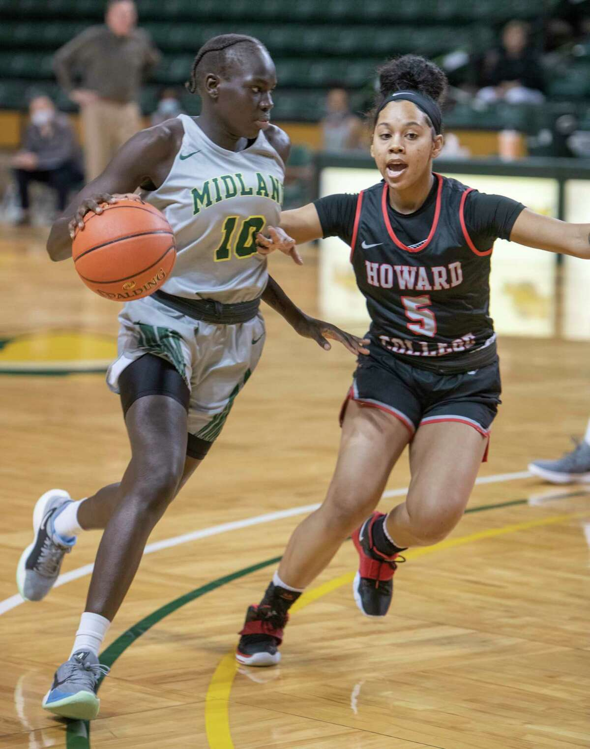Midland College's Nya Lok looks to drive the lane around Howard College's Tatym Barnes 03/06/2021 at Chaparral Center. Tim Fischer/Reporter-Telegram
