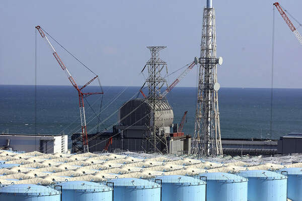 Rows of storage tanks holding treated but still contaminated water stand near the Fukushima Daiichi nuclear plant's No. 3 reactor building on Feb. 4, 2021.
