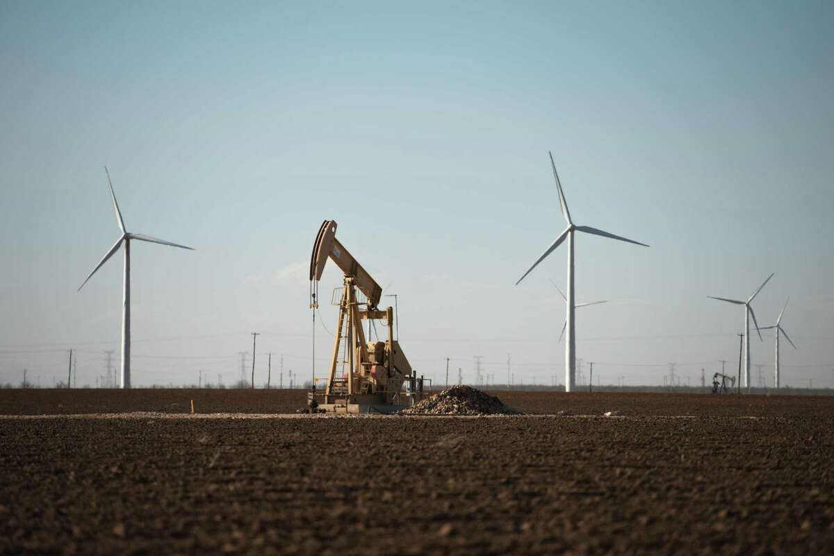 FILE - An oil pump jack and wind turbines near Stanton, Texas, on Feb. 21, 2019. A day after Democratic presidential nominee Joe Biden called for a transition away from oil and natural gas, industry executives said the country would need fossil fuels for decades to come. (Brandon Thibodeaux/The New York Times)