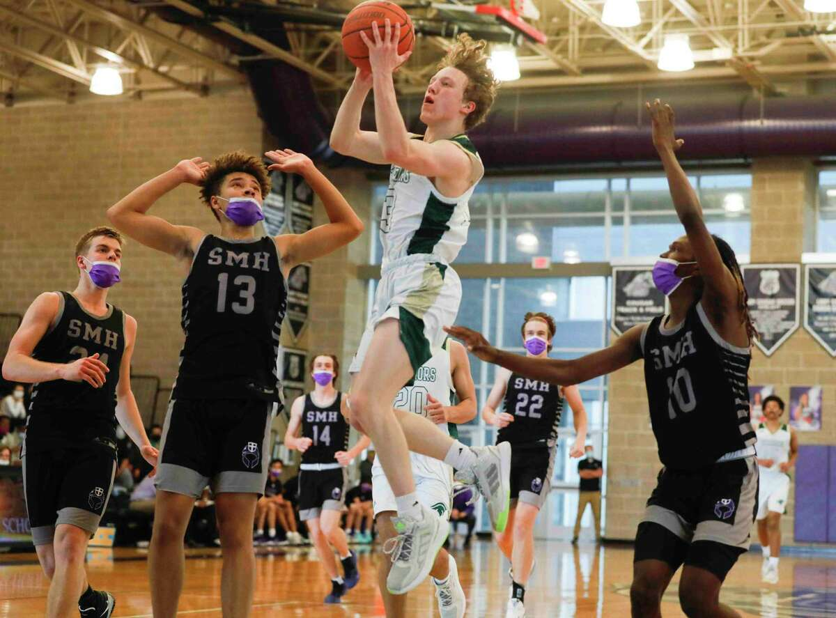 The Woodlands Christian Academy's Austin Benigni (13) shoots a layup past Saint Mary's Hall's Gavin Walker (13) and Rodney Hunter (10) during the third quarter of a TAPPS Class 5A regional playoff game at College Station High School, Saturday, March 6, 2021, in College Station.