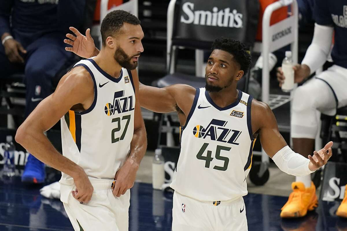 Utah Jazz's Donovan Mitchell (45) and Rudy Gobert (27) walk on the court in the second half during an NBA basketball game against the Milwaukee Bucks Friday, Feb. 12, 2021, in Salt Lake City. (AP Photo/Rick Bowmer)