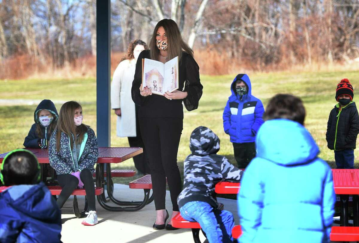 Shelton's Director of Curriculum Kristen Santilli reads to students in Tracey Sedlock's 1st grade class in the outdoor classroom at Mohegan School in Shelton on Jan. 19.