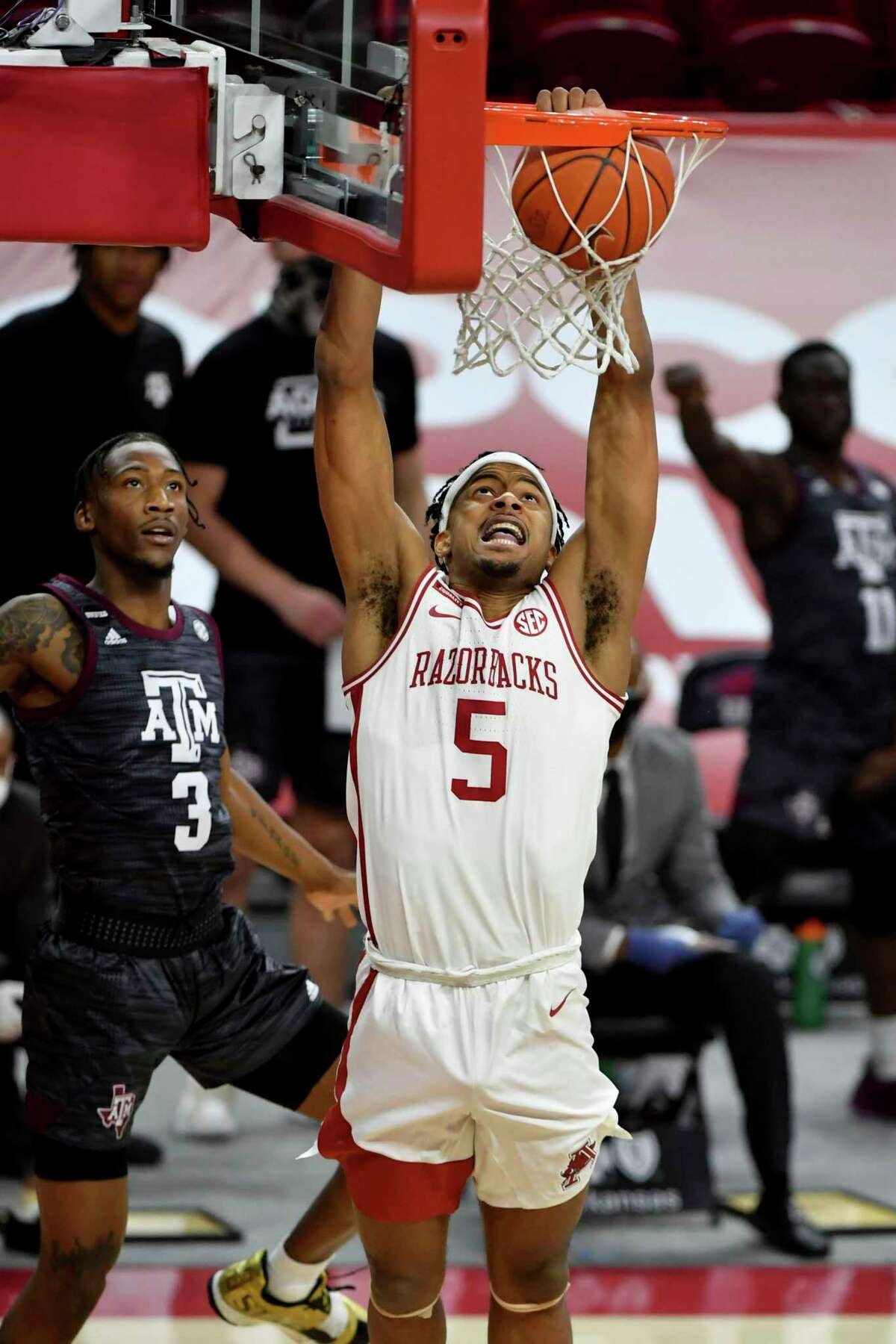 Arkansas guard Moses Moody (5) dunks the ball in front of Texas A&M defender Quenton Jackson (3) during the first half of an NCAA college basketball game in Fayetteville, Ark., Saturday, March 6, 2021. (AP Photo/Michael Woods)
