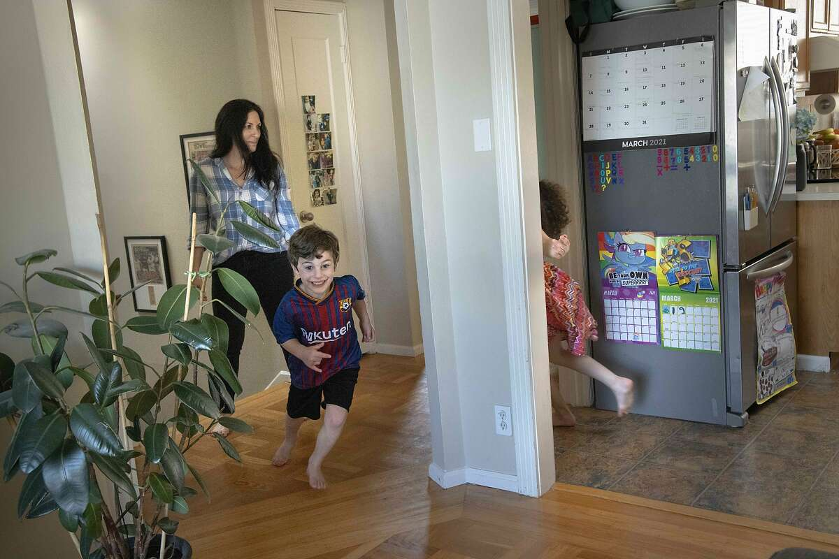 Nate, 5, is chased by sister Bayla, 7, with mom Erica Kajdasz in the hallway.