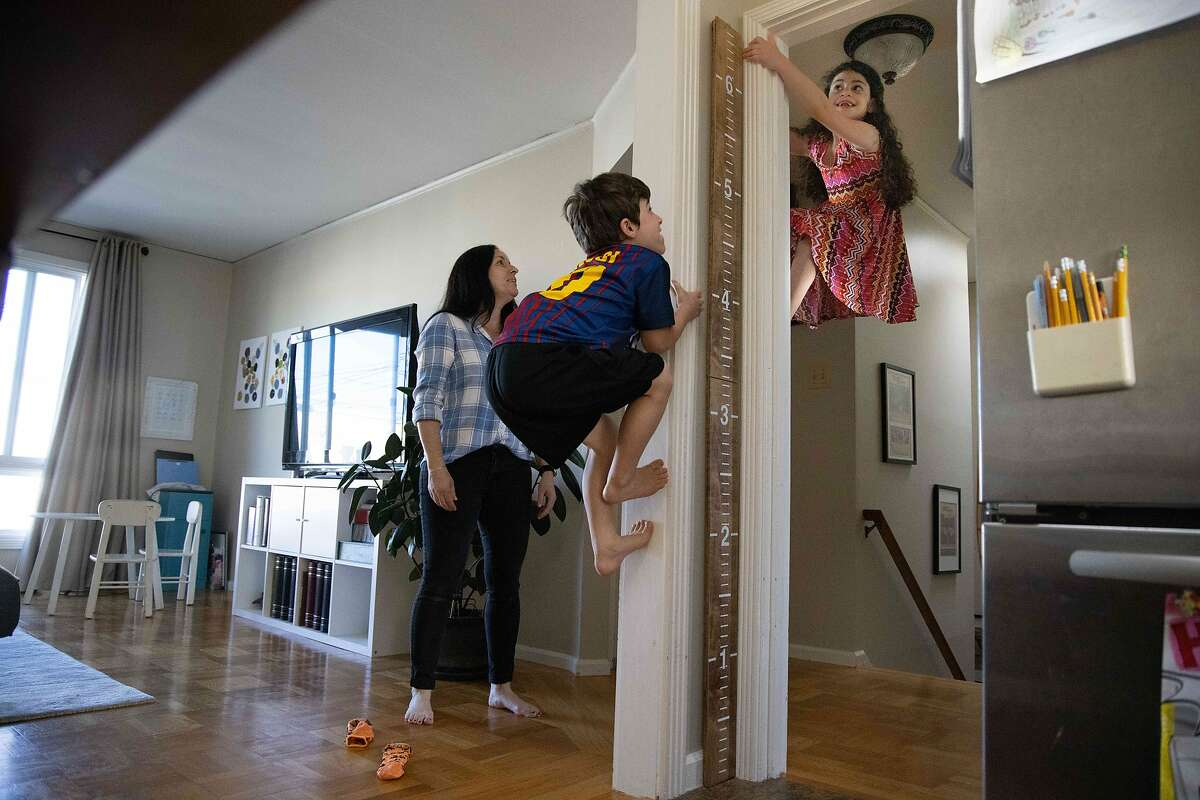 Nate, 5, and sister Bayla, 7, climb a wall as mother Erica Kajdasz watches.
