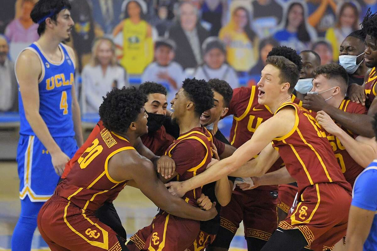 UC guard Tahj Eaddy (center) celebrates with teammates as UCLA guard Jaime Jaquez Jr. walks off after Eaddy's game-winning shot.