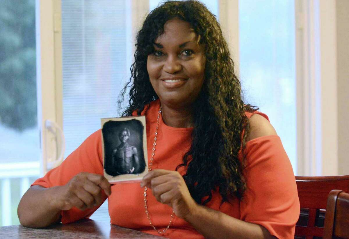 FILE - In this July 17, 2018, photo, Tamara Lanier holds an 1850 photograph at her home in Norwich, Conn., of a South Carolina slave named Renty, who Lanier said is her family's patriarch. The portrait was commissioned by Harvard biologist Louis Agassiz, whose ideas were used to support the enslavement of Africans in the United States. In March 2019, Lanier filed a lawsuit in Massachusetts state court demanding that Harvard turn over the photo and pay damages. In March 2021, a Massachusetts Superior Court judge dismissed the suit. (John Shishmanian/The Norwich Bulletin via AP, File)
