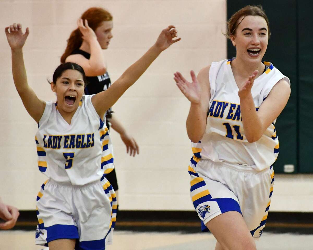 Plainview Christian Academy players Lucie Ragland (left) and Soraya Davey celebrate the Lady Eagles' 34-27 victory over Wichita Falls Christian in the regional round of the TAPPS Class 1A girls basketball playoffs on Saturday at Guthrie.