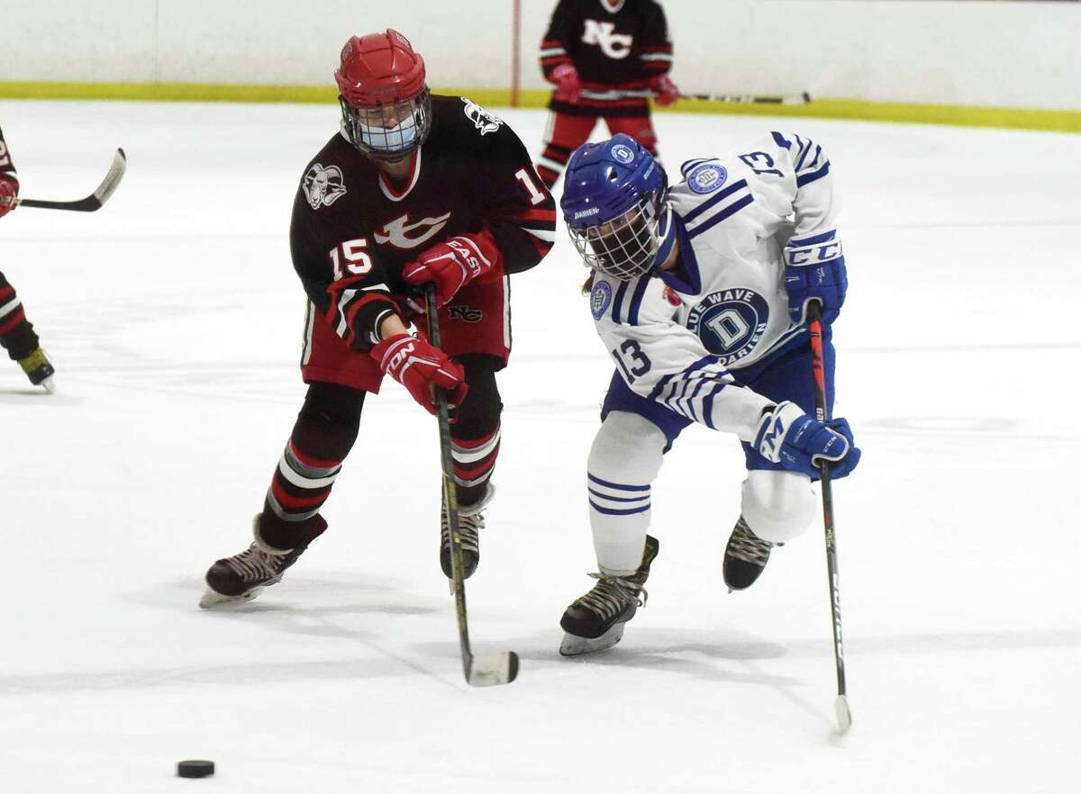 New Canaan's Caitlin Tully (15) and Darien's Ceci Stein (13) race for the puck during a girls ice hockey game at the Darien Ice House on Saturday, March 6, 2021.