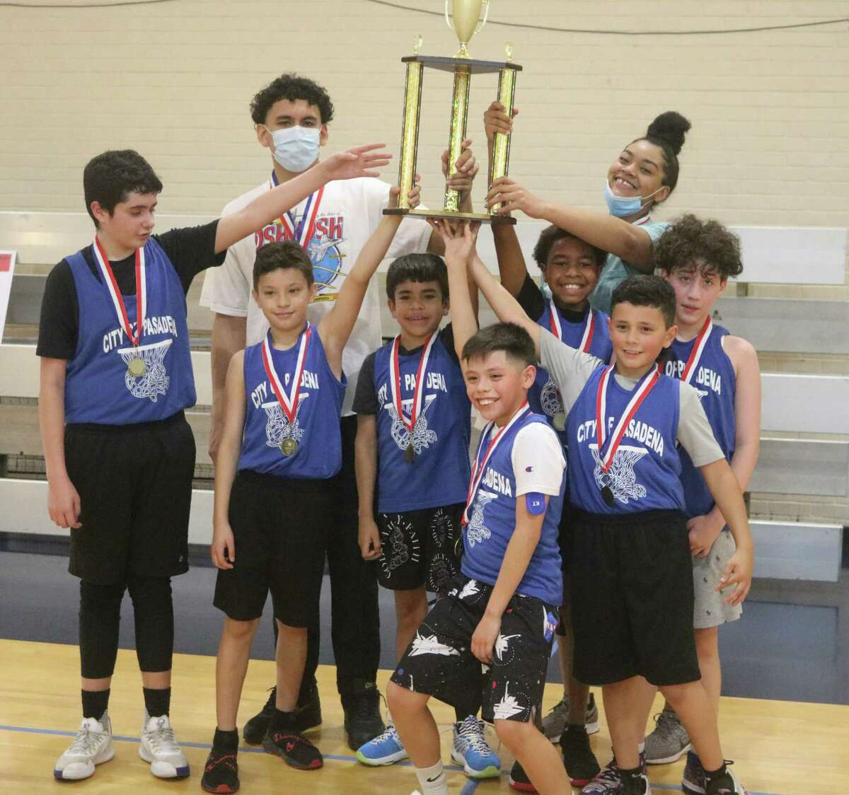 Members of the Faith basketball team hoist their city championship trophy after winning the 11 and 12-year-old division at PAL Gym Saturday.