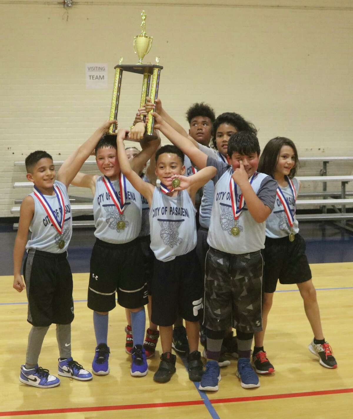 The Ball Starts, the 7 and 8-year-old city champs, raise their trophy at PAL Gym Saturday night.