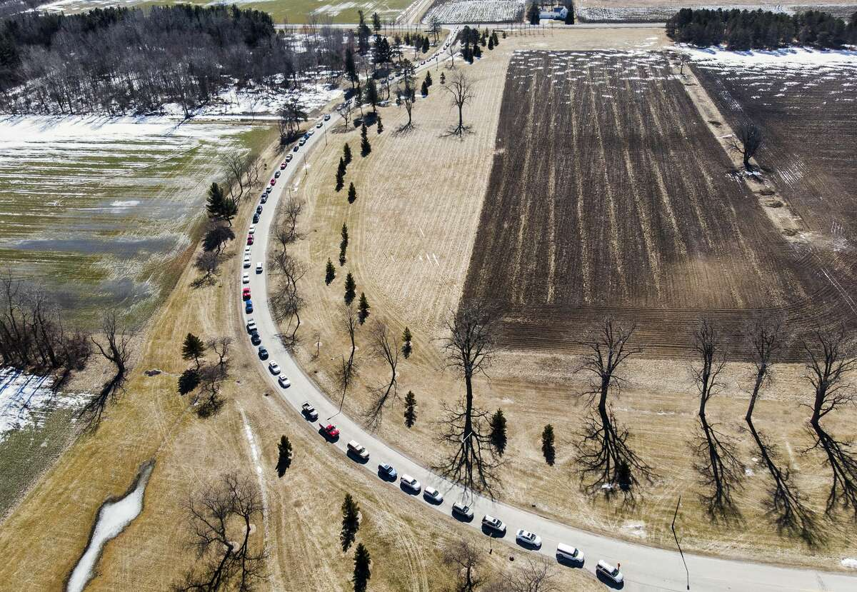 Vehicles line up for a vaccination clinic hosted by Delta College, the Michigan National Guard and the tri-counties' health departments, aimed at vaccinating 3,000 people over the weekend, Saturday, March 6, 2021 at Delta College. (Adam Ferman/for the Daily News)