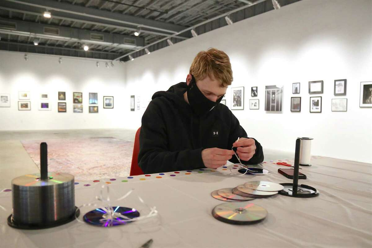 Ben Larsson, 17, of Westport, helps with the art project at the Winter Outdoor Lights Festival at MoCA Westport on Saturday, March 6, 2021.