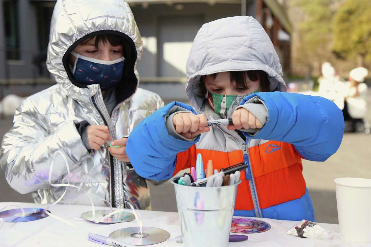 Aiden Chen, 7, of Fairfield, left, helps his brother Liam, 5, at the Winter Outdoor Lights Festival at MoCA Westport on Saturday, March 6, 2021.