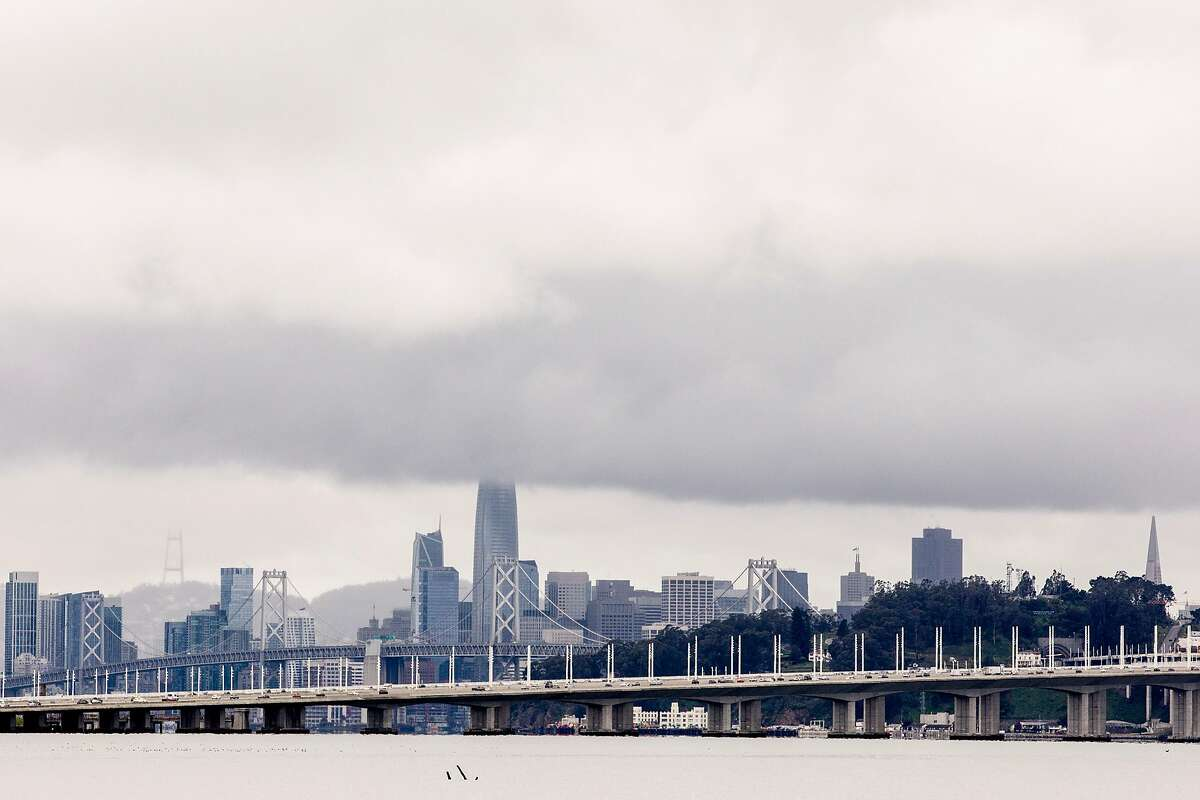 The San Francisco skyline sits under a dark rain cloud as seen from Emeryville, Calif. Saturday, March 7, 2020. After an entire month with no wet weather, Bay Area residents woke up to much anticipated rain showers Saturday morning.
