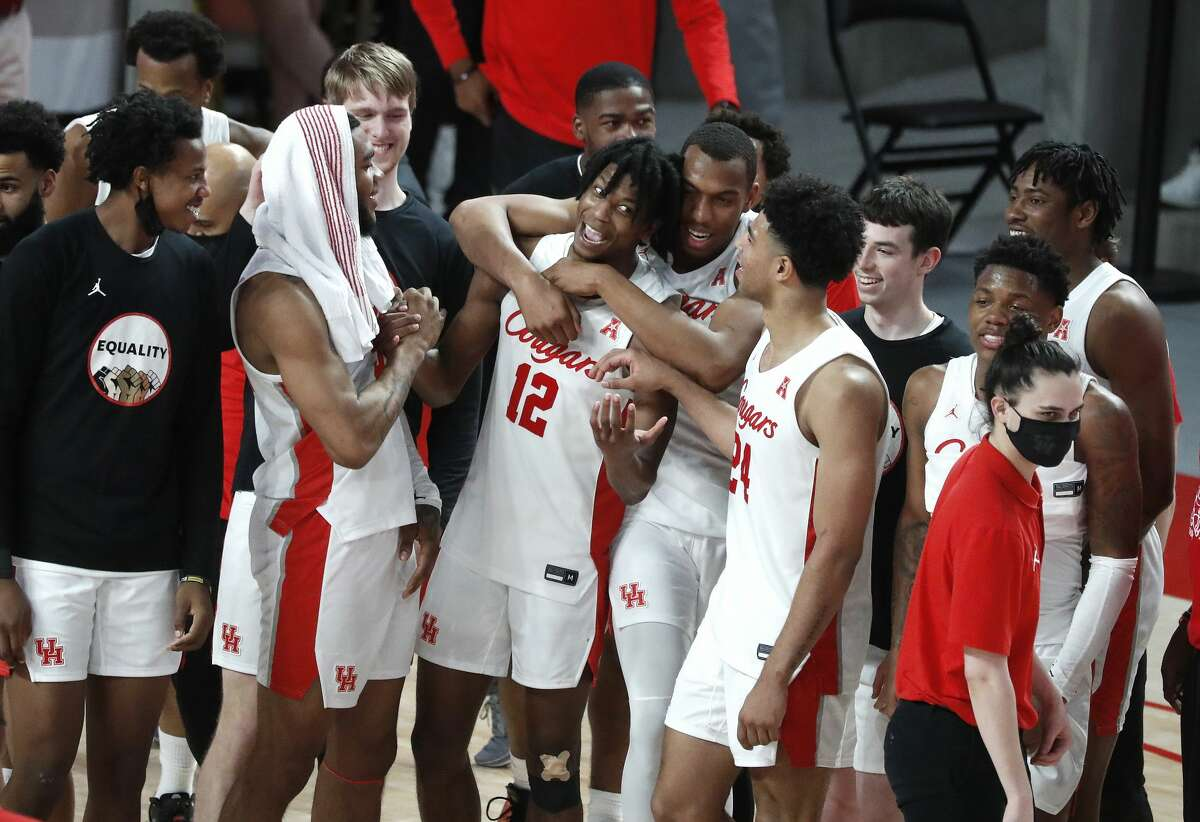 Houston Cougars guard Tramon Mark (12) is hugged by teammates after he shot his game-winning three-pointer at the buzzer as Cougars beat Memphis Tigers 64-76 after an NCAA Men's basketball game at the Fertitta Center, Sunday, March 7, 2021, in Houston.