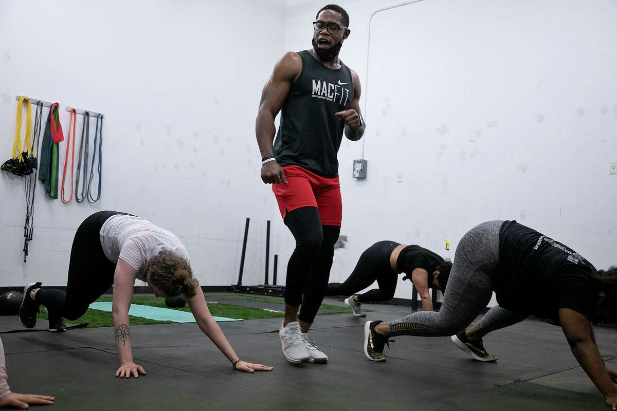 Patrick McDonald Jr., co-owner of MacFit Athletics, instructs and encourages clients during a group fitness class at MacFit Athletics in San Antonio on March 4, 2021.