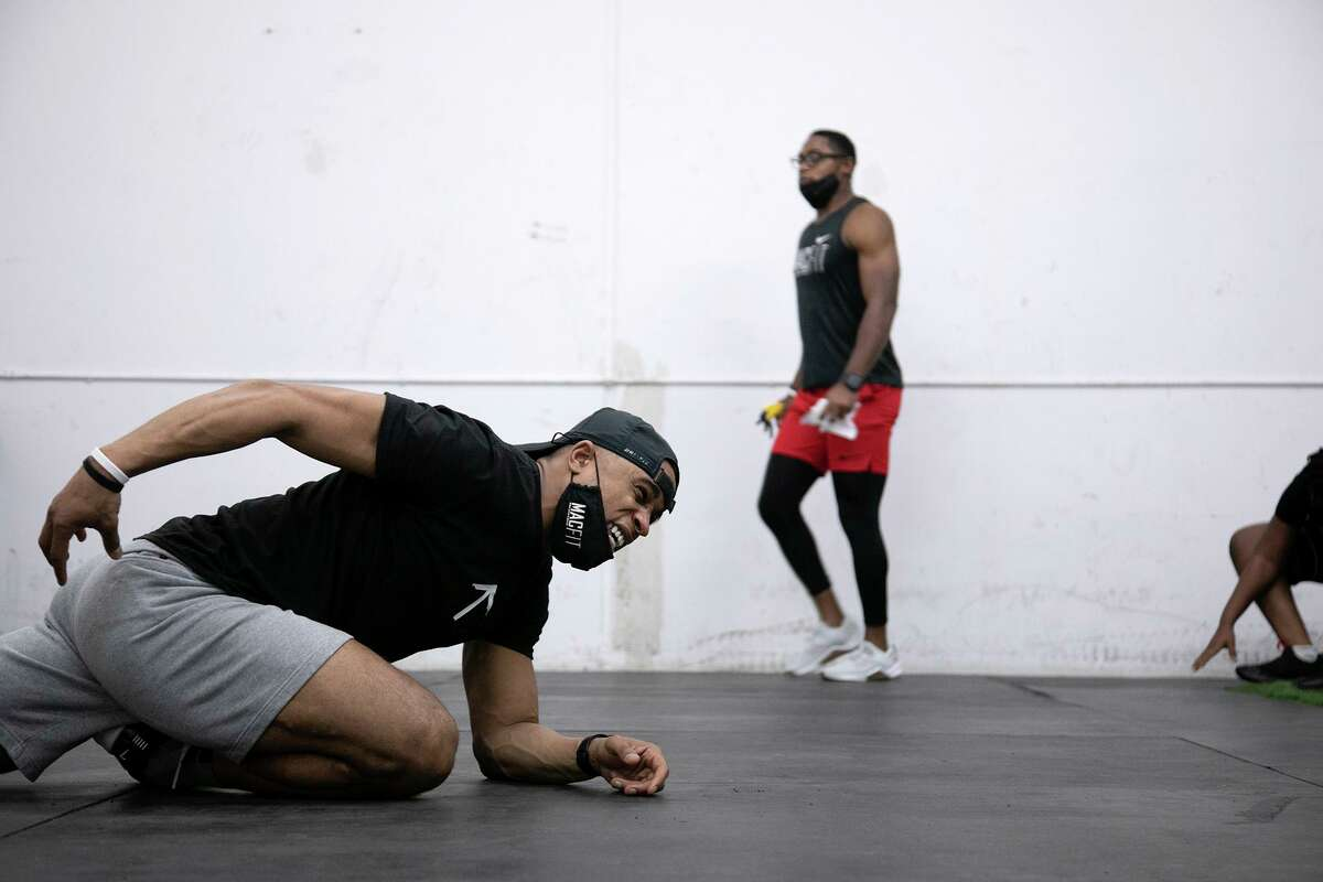 Patrick McDonald, co-owner of MacFit Athletics, demonstrates a stretch at the conclusion of a group fitness class at MacFit Athletics in San Antonio on March 4, 2021. In the background is McDonald's brother and co-owner, Patrick McDonald Jr.
