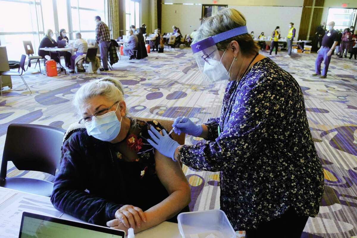 Pat Lambert, left, is given her first does of the Pfizer Covid-19 vaccine by registered nurse Janet Chen at the mass vaccination POD at Rivers Resort and Casino on Sunday, March 7, 2021, in Schenectady, N.Y. The vaccines were allocated to Schenectady county specifically for county residents 65 year of age or older. Those who received the vaccine on Sunday were also signed up for their second dose again at Rivers in 21 days. County officials said that they planned on vaccinating 1,100 people on Sunday. (Paul Buckowski/Times Union)