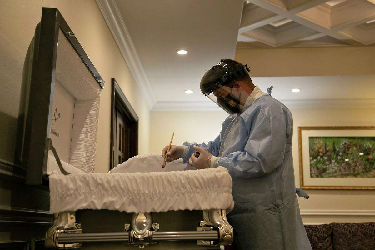 Funeral director Tim Puchner applies cosmetics to a body before a visitation at Mission Park Funeral Chapels Cherry Ridge in San Antonio on Feb. 25, 2021.