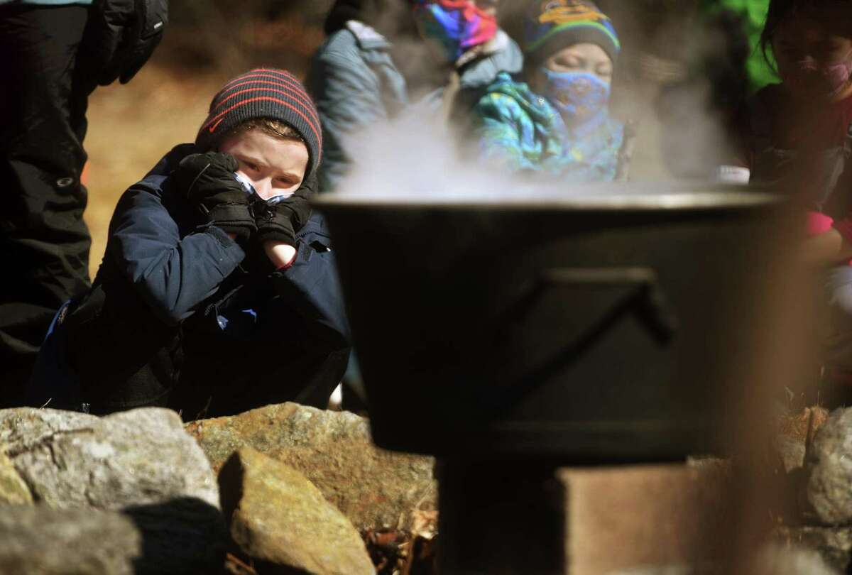 Lucas Peck, 7, of Monroe, watches a pot of maple sap boil over an open fire during a maple sugaring demonstration at the Nature and Arts Center in Trumbull, Conn. on Sunday, March 07, 2021.