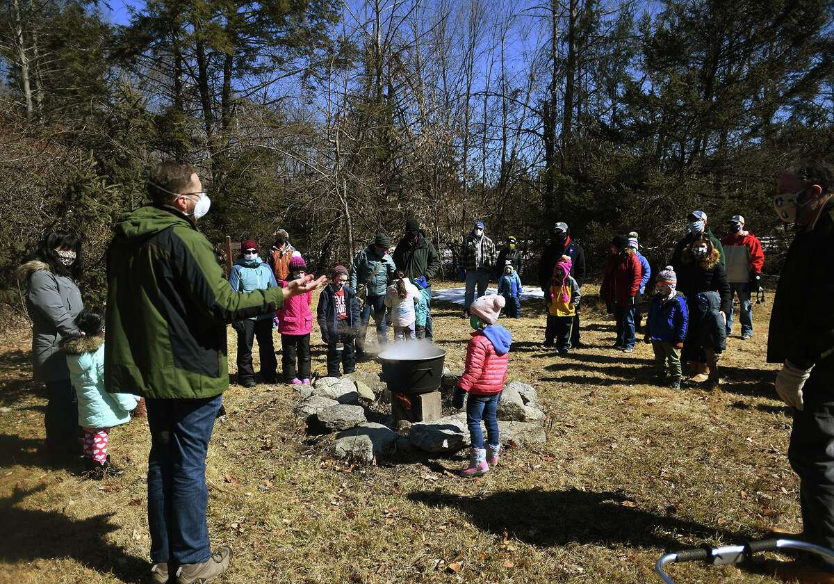 Nature and Arts Center instructor Mark Ceneri, left, leads a maple sugaring demonstration at the center in Trumbull, Conn. on Sunday, March 07, 2021.