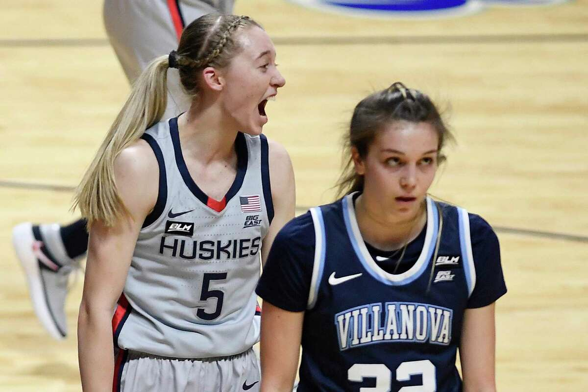 Connecticut's Paige Bueckers, left, and Villanova's Bella Runyan, right, react to a foul called against Villanova during the first half of an NCAA college basketball game in the Big East tournament semifinals at Mohegan Sun Arena, Sunday, March 7, 2021, in Uncasville, Conn. (AP Photo/Jessica Hill)